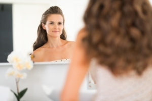 39441128 - happy young woman looking in mirror in bathroom