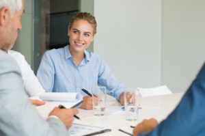 58217480 - young cheerful business woman making notes during a meeting. businesswoman listening to senior businessman while in meeting. happy young business woman in a brainstorming with colleague in office boardroom.